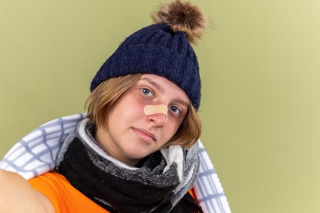 Jeune femme malsaine avec un chapeau chaud et une écharpe autour du cou enveloppée dans une couverture souffrant de froid avec un patch sur le nez souriant debout sur un mur vert