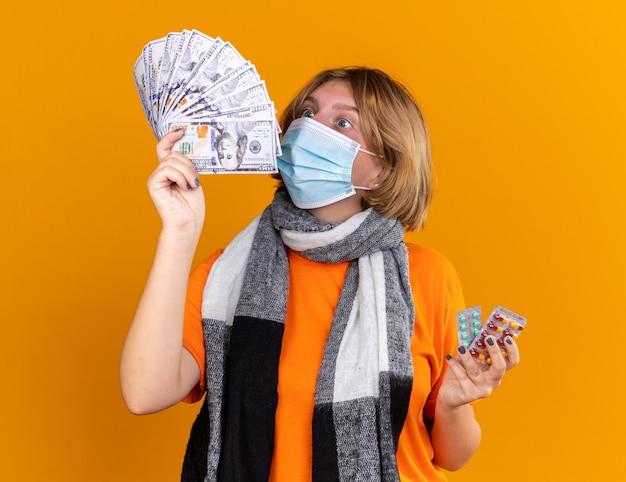 Jeune femme malsaine avec une écharpe chaude autour du cou portant un masque facial protecteur tenant des pilules et de l'argent, l'air surprise et confuse debout sur un mur orange