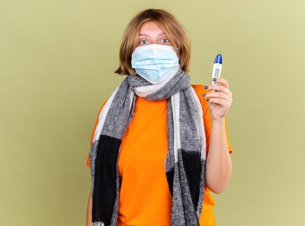 Jeune femme malsaine avec une écharpe chaude autour du cou portant un masque facial de protection souffrant de rhume et de grippe tenant un thermomètre ayant de la fièvre l'air inquiet debout sur un mur vert