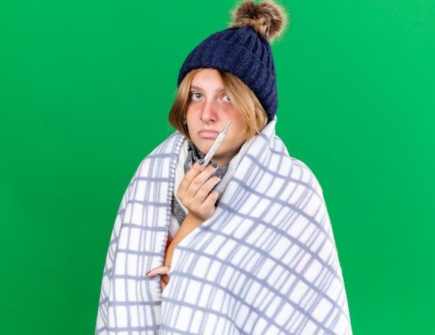 Jeune femme malsaine enveloppée dans une couverture portant un chapeau mesurant sa température corporelle à l'aide d'un thermomètre souffrant de grippe ayant de la fièvre debout sur un mur vert