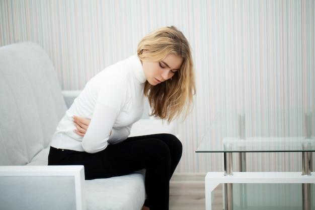 Jeune femme malsaine avec maux d'estomac s'appuyant sur le canapé à la maison