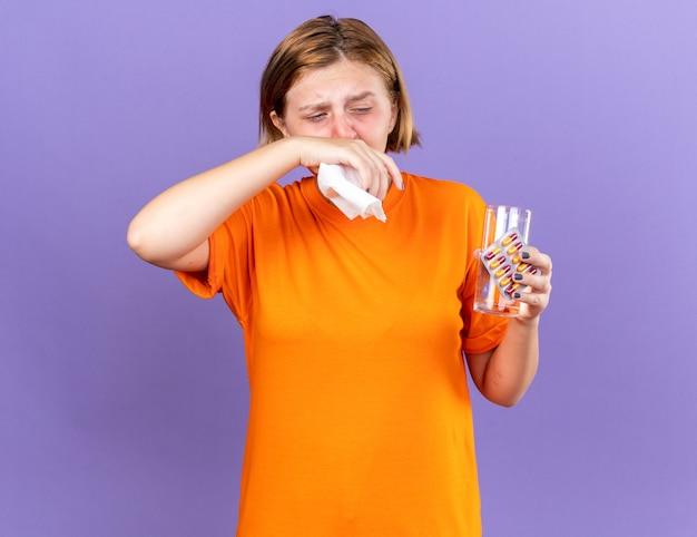 Jeune femme malsaine en t-shirt orange avec un verre d'eau et des pilules se sentant terriblement soufflant le nez qui coule a attrapé le froid en éternuant dans un tissu debout sur un mur violet