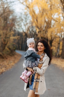 Jeune femme maman joue avec sa petite fille au parc automne