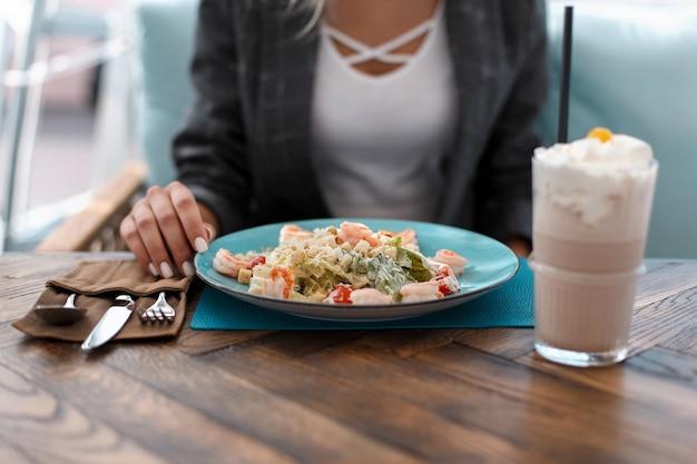 Jeune femme mange une salade césar et boit un milkshake dans un restaurant