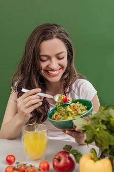 Jeune femme mangeant des aliments sains à fond vert