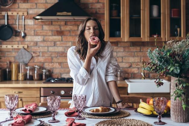 Jeune femme mangeant un beignet avec plaisir dans la cuisine.