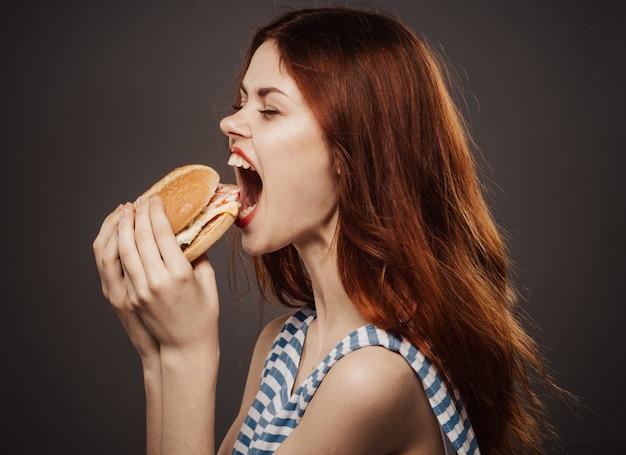 Jeune femme mangeant un hamburger juteux, délicieux hamburger de restauration rapide en studio