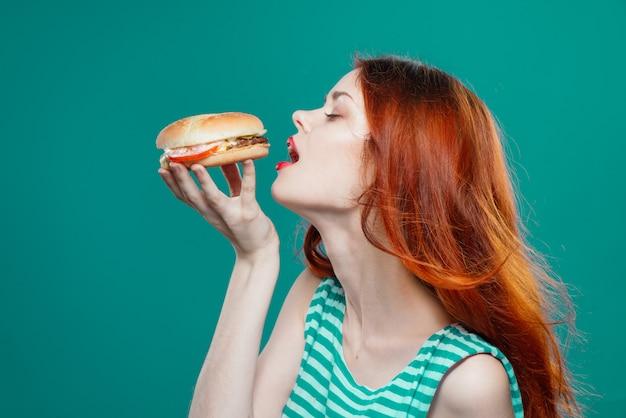 Jeune femme mangeant un hamburger juteux, délicieux hamburger de restauration rapide