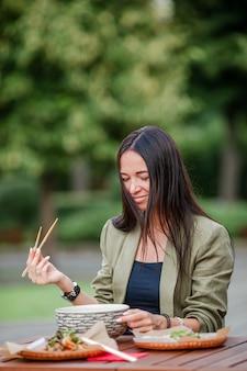 Jeune femme mangeant des nouilles à emporter dans la rue