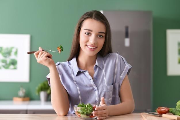Jeune femme mangeant une salade saine avec des légumes dans la cuisine