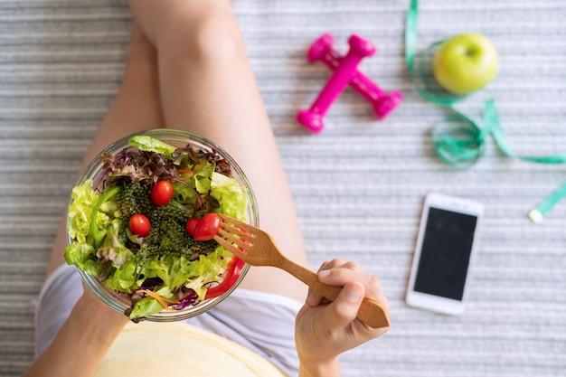 Jeune femme mangeant une salade saine maison à la maison