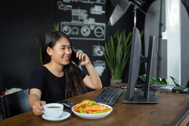 Jeune femme, manger, croissant, sandwichs, dans, bureau, salle