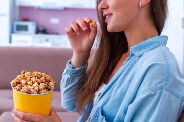 Jeune, femme, manger, croquant, caramel, pop-corn, regarder, tv, maison