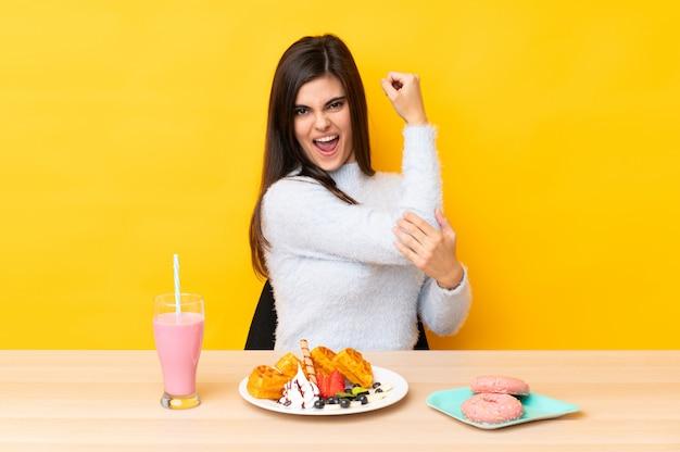 Jeune, femme, manger, gaufres, milkshake, table, mur, jaune, confection, fort, geste