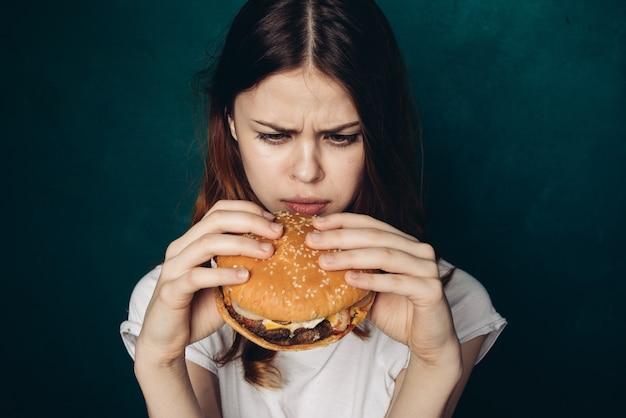 Jeune femme, manger, a, hamburger