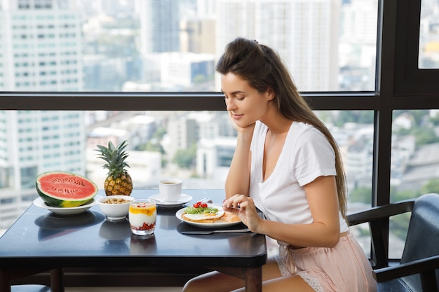 Jeune, femme, manger, petit déjeuner, matin