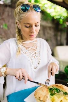 Jeune femme, manger, sandwich, à, couteau couteau, et, fourchette