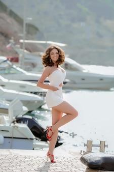 Une jeune femme mannequin dans une robe courte blanche se promène dans une baie près de la mer avec des yachts.