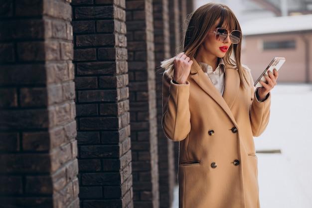 Jeune femme en manteau beige à l'aide de téléphone dans la rue