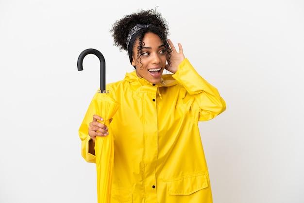 Jeune femme avec manteau imperméable et parapluie isolé sur fond blanc écoutant quelque chose en mettant la main sur l'oreille