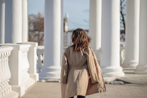 Une jeune femme en manteau léger marche dans la ville