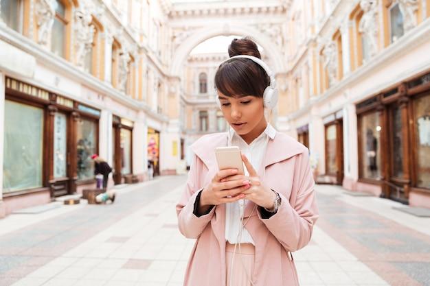 Jeune femme en manteau rose, écouter de la musique avec des écouteurs à l'extérieur