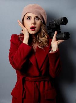 Jeune femme en manteau rouge avec des jumelles