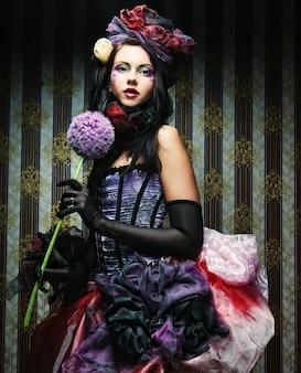 Jeune femme avec maquillage créatif dans un style poupée avec fleur