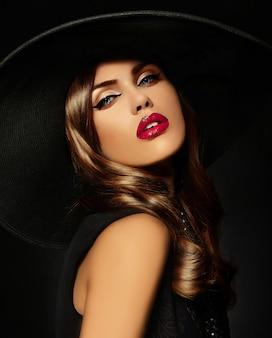 Jeune femme avec maquillage lumineux et chapeau noir