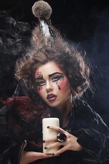 Jeune femme avec maquillage lumineux portant un costume de carnaval tenant une bougie. image d'halloween.