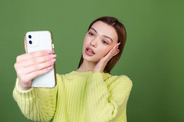 Jeune femme avec un maquillage naturel parfait, de grandes lèvres brunes sur un mur vert avec un téléphone portable, prendre un selfie en se photographiant