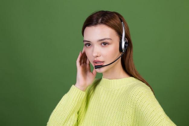 Jeune femme avec un maquillage naturel parfait, de grandes lèvres brunes en pull décontracté sur un mur vert dans les écouteurs, le directeur du centre d'appels, les appels d'invitation positifs, aident à soutenir