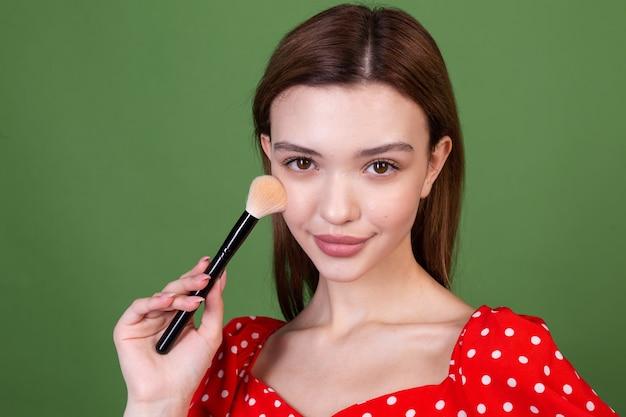 Une jeune femme avec un maquillage naturel parfait, de grandes lèvres brunes en robe rouge à pois sur un mur vert, tient un portrait de beauté de mode pinceau blush