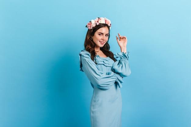 Jeune femme avec maquillage nude et fleurs dans ses cheveux. dame en robe bleu ciel posant sur un mur isolé.