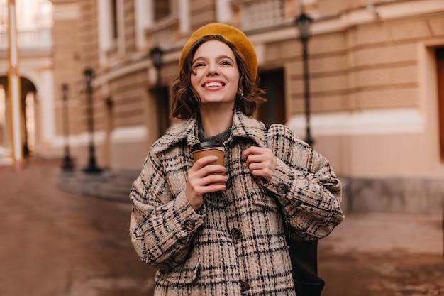Jeune femme avec un maquillage nude sourit sincèrement contre le mur de la ville
