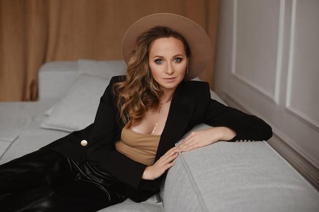 Une jeune femme avec un maquillage parfait et des yeux bleus profonds portant un chapeau à la mode et un blazer noir assis sur le canapé à l'intérieur et regardant la caméra