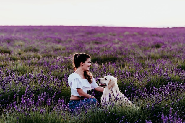 Jeune femme marchant sur un champ de lavande pourpre avec son chien golden retriever au coucher du soleil. animaux à l'extérieur