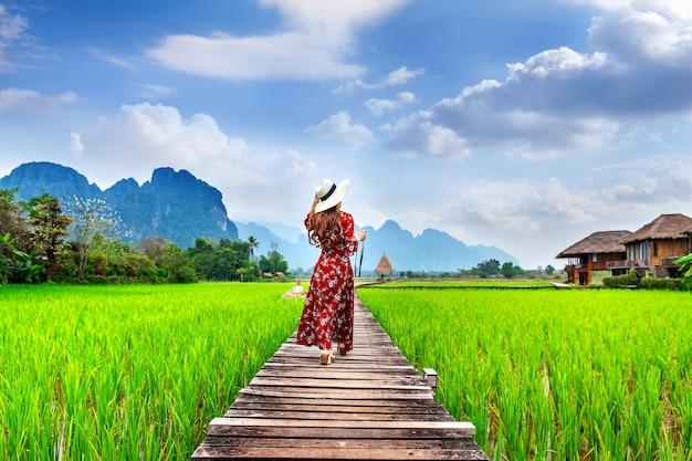 Jeune femme marchant sur un chemin en bois avec champ de riz vert à vang vieng, laos.
