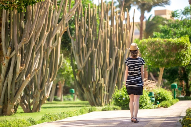 Jeune femme marchant à côté des cactus
