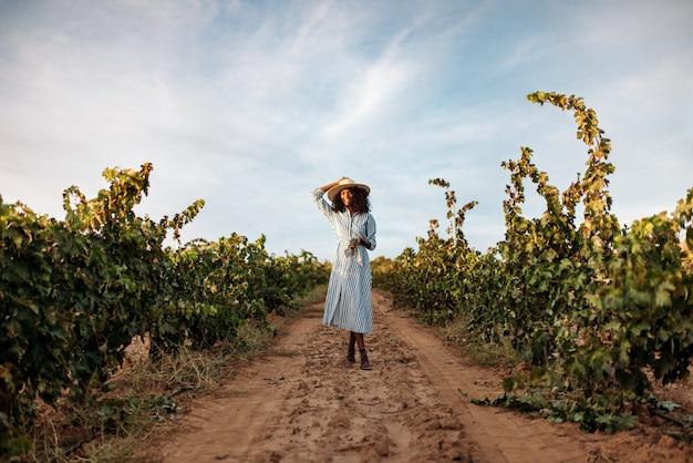 Jeune femme marchant dans un chemin au milieu d'un vignoble