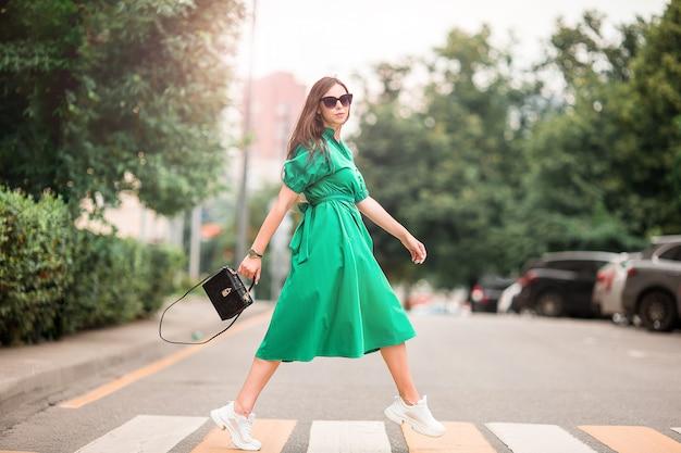 Jeune femme marchant dans la ville de l'autre côté de la rue