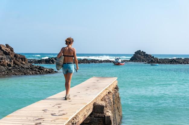 Une jeune femme marchant le long de la passerelle en bois sur l'isla de lobos, le long de la côte nord de l'île de fuerteventura, îles canaries. espagne