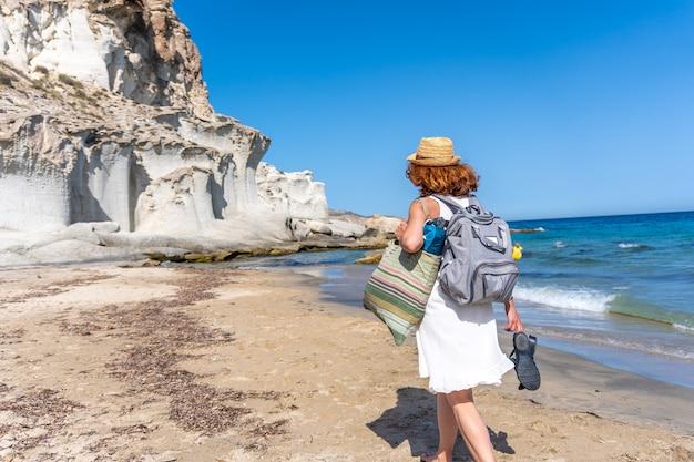 Une jeune femme marchant le long de la plage d'enmedio à cabo de gata par une belle journée d'été, almeria