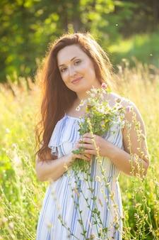 Jeune femme marchant parmi les fleurs sauvages aux beaux jours d'été