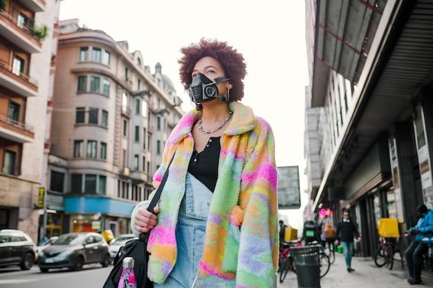 Jeune femme marchant en plein air à milan portant un masque médical protégeant de la pollution et des virus