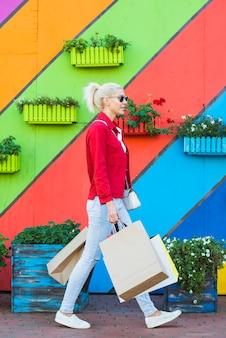 Jeune femme marchant avec des sacs près du mur