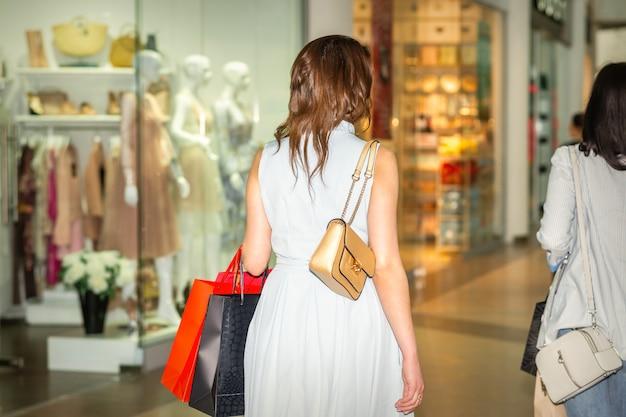 Jeune femme marchant avec des sacs à provisions