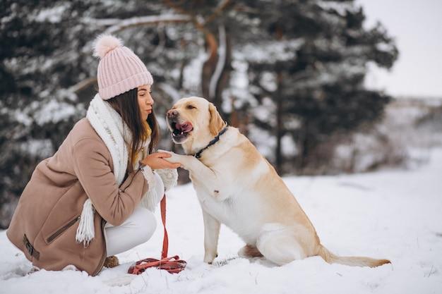 Jeune femme marchant avec son chien dans un parc d'hiver