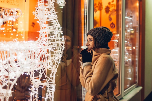 Jeune femme marchant en ville et regardant des vitrines de noël décorées la nuit.
