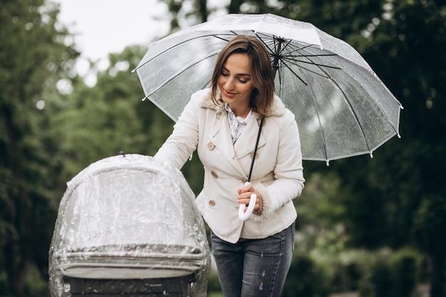 Jeune, femme, marche, bébé, landau, parapluie, mauvais temps